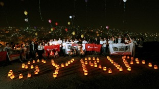 "Syrian refugees in Ammam release balloons and form the word ""Syria"" with candles to mark the second anniversary"