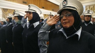Iraqi policewomen salute as the Iraqi national anthem is played during a ceremony celebrate International Women's Day in Baghdad in 2009