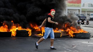 A protester burns tyres used to set up road blocks during clashes with riot police