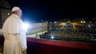 Pope Francis greets the crowds from the balcony of St Peter's Basilica
