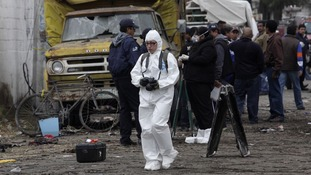 A member of the forensics team walks near the site of the explosion.