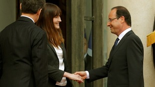 France's former First Lady Carla Bruni shakes hands with incoming President Francois Hollande