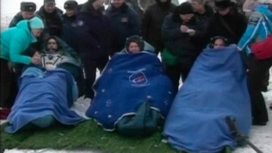 NASA's Kevin Ford and Russian cosmonauts Oleg Novitskiy and Evgeny Tarelkin wrapped in blankets after leaving the Soyuz space capsule