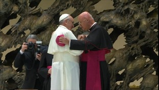 Pope Francis greets a cardinal at the press conference