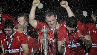 Welsh players Leigh Halfpenny (left), Gethin Jenkins (centre) and Alex Cuthbert (right) celebrate after lifting the trophy.
