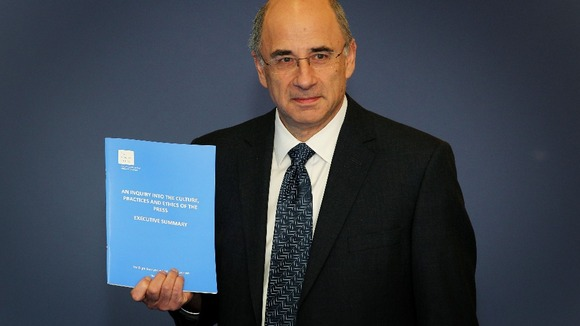 Lord Justice Leveson with the Report from the Inquiry into the Culture, Practices and Ethics of the Press.