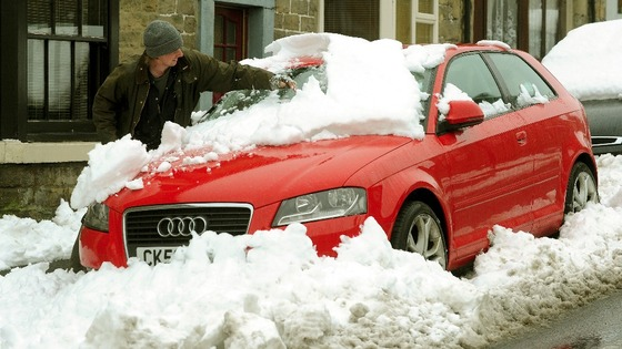 A man clears of the snow of his car in Bowes County Durham