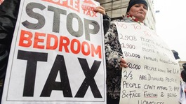 Protesters hold up signs against the bedroom tax