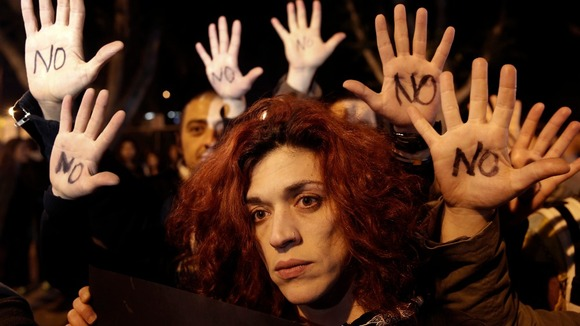 "Anti-bailout protesters raise their open palms showing the word ""No"" after Cyprus' parliament"