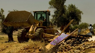 A bulldozer drives past a demolished makeshift structure in the unauthorised outpost of Ramat Migron