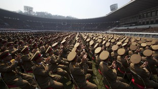 A crowd of North Korean military members applaud the country's leader Kim Jong Un.