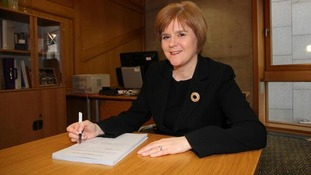Nicola Sturgeon smiles as she signs the Bill.