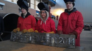 The apprentices hold up their handy work with the referendum date etched in steel.