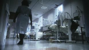 Nurse walking along in hospital ward