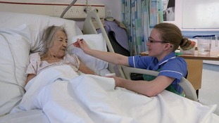Nurse feeding old lady in hospital bed