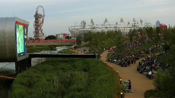 People sit in the Olympic Park and watch the swimming event on a huge TV-Screen in front of the Olympic Stadium during the Games