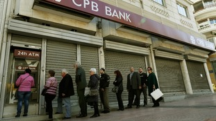Customers queue to take out cash from the Cyprus Popular Bank