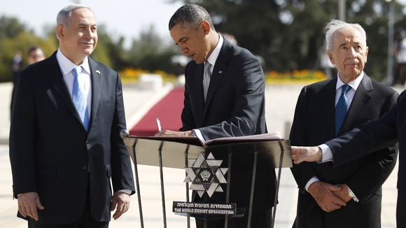 President Obama, flanked by Israel's President Shimon Peres (R) and Prime Minister Benjamin Netanyahu, writes in a guest book