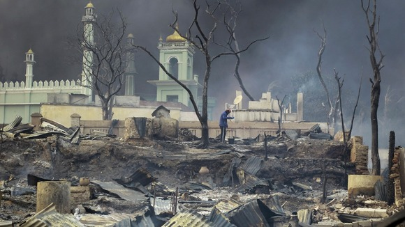 A man stands in front of a burnt-out mosque in Meikhtila, central Myanmar