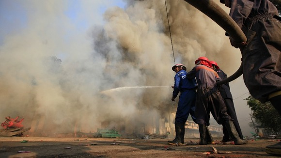 Firefighters attempt to extinguish a fire during riots in Meikhtila