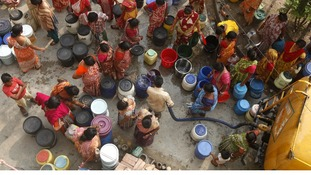People collect drinking water from a water tanker in Kolkata, India