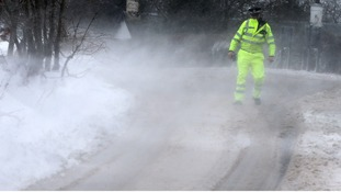 A police officer struggles in the wind and snow whilst attending an accident.