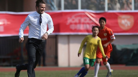 David Beckham plays football on a sports field during his visit in Qingdao