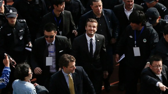 David Beckham makes his way into a sports field with help of security personnel