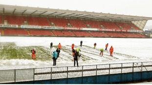 Ground staff help clear snow away from Windsor Park on Friday