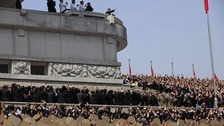 North Koreans react as North Korean leader Kim Jong Un, at top center, waves to them at the end of a mass military parade.