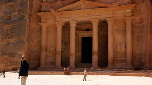 President Barack Obama is dwarfed as he visits Jordan's ancient city of Petra.