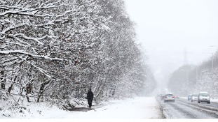 A man walks along a snowy road in Leeds, Yorkshire.