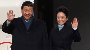 Chinese President Xi Jinping and First Lady Peng Liyuan wave as they disembark from a plane upon their arrival at Moscow's Vnukovo airport.