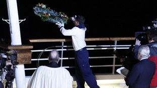 A crew member throws a wreath overboard during a memorial service, marking the 100th year anniversary of the Titanic disaster.