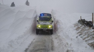 An Oldham Mountain Rescue vehicle drives through a snow drift.