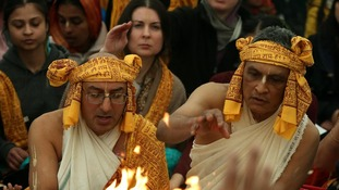 Hare Krishna priests pour sanctified offering of clarified butter into a sacred fire.