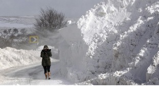 A person walks past a snow drift in the Glens of Antrim as wintry weather continues to cause havoc.