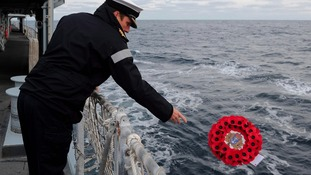 A sailor on the HMS Edinburgh lays a wreath in the mid Atlantic in memory of HMS Beverley