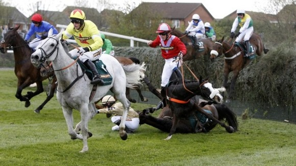 According to Pete ridden by Harry Haynes (in red) falls after jumping Becher's Brook in the Grand National
