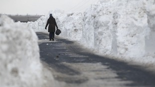 A farmhand makes her way through a wall of snow piled up along a road in the Briercliffe area of Burnley