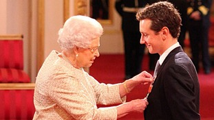 Alistair Brownlee receives his MBE from the Queen.