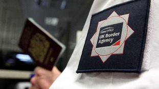 File photo of a UK Border Agent with a passport.