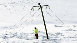 An engineer walks past a damaged power line in Kintyre in Scotland
