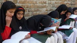 Girls read their schoolbooks in the Swat Valley in 2009