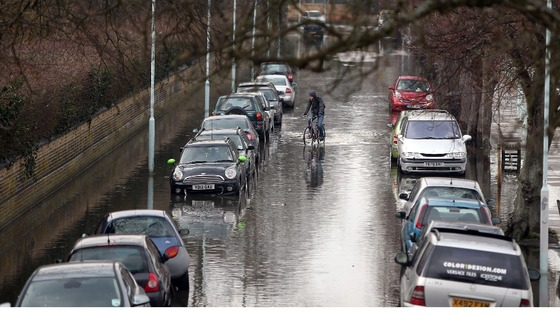 A cyclist rides down Ranelagh Drive in Richmond which was briefly flooded due to spring tides leaving parked cars under water