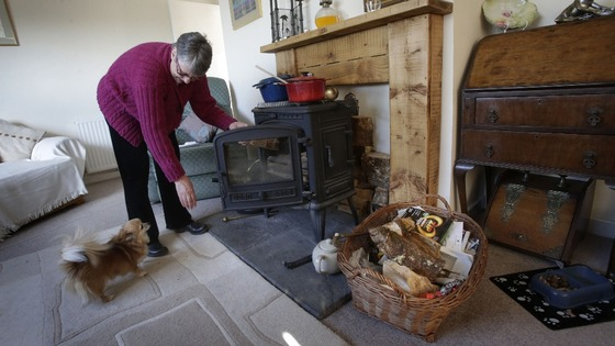 Janette Hamilton cooks on a wood burning stove at her home in Southend in Scotland after loosing her power supply