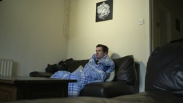 Man sits on sofa wrapped in blanket