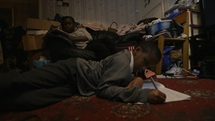 Young boy does homework on floor in crowded room