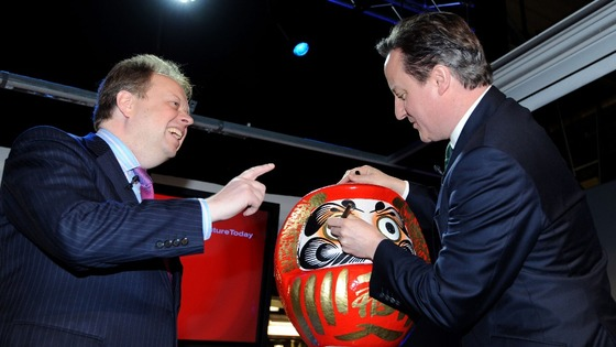 David Cameron colours in the eye of a Daruma doll