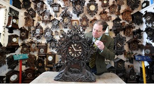 Roman Piekarski adjusts a particularly ornate cuckoo clock